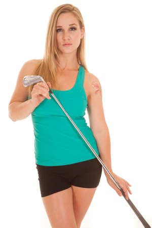 A woman holding a golf club with a serious expression. photo