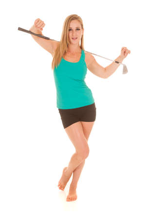 A woman holding a golf club on her shoulders. photo