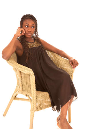 A woman with her hand by her face sitting in a wicker chair in her black dress. photo