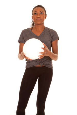 a woman holding on to a volleyball looking up. photo