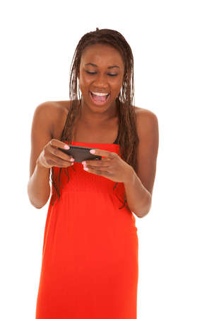 A woman with a smile on her face using her phone to text a friend. photo