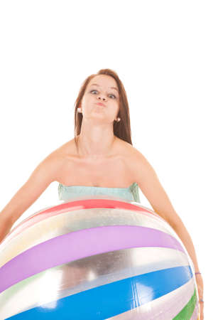 A girl is holding a beach ball with a crazy face.