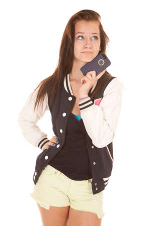 A teenager is holding her cell phone by her chin. photo