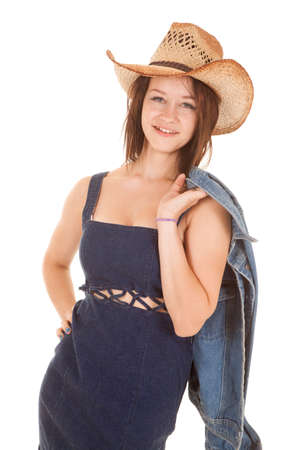 A cowgirl is holding a jacket while smiling. photo