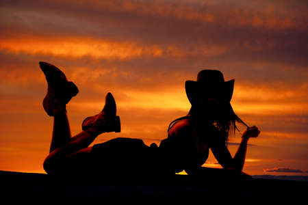 A silhouette of a cowgirl is laying on her stomach.