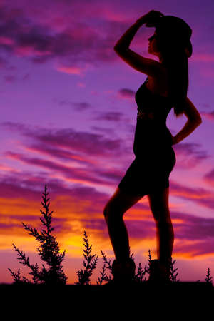 A silhouette of a cowgirl with a hat and boots. photo