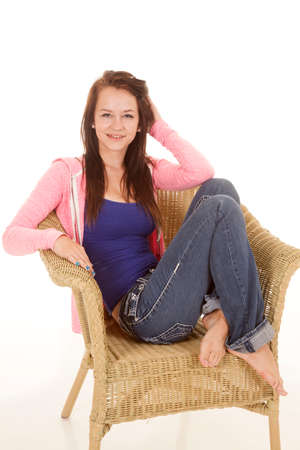 A girl in a pink jacket is sitting in a wicker chair.  photo
