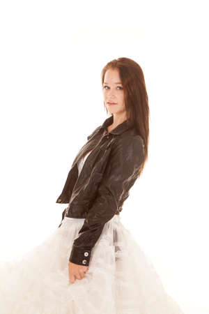 A girl is in a black leather jacket with a white fluffy skirt. photo