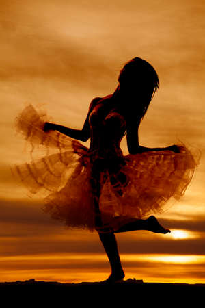 A silhouette of a woman kicking up her leg. photo
