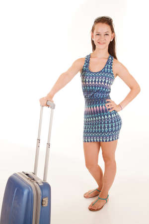 A teen is standing with her luggage.