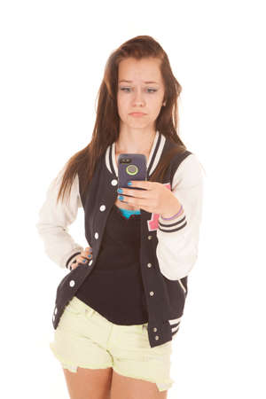 pouty: A girl holding her cell phone has a pouty face.