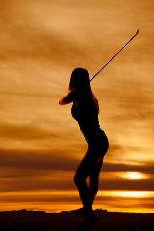 A silhouette of a woman swinging her golf cub in the outdoors. Imagens