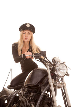 A police woman is kneeling on the seat of her bike. Stockfoto