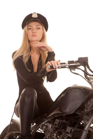 A woman cop is sitting on her motorcycle with her hand under her chin. photo