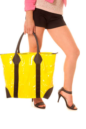 A womans legs with a yellow bag. photo