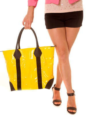 A womans legs crossed while holding a yellow handbag. photo
