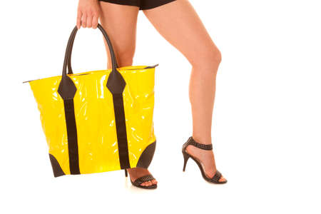 A womans leg bent while holding a yellow bag. photo