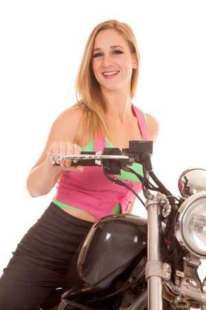 A woman is sitting on her motorcycle smiling. photo