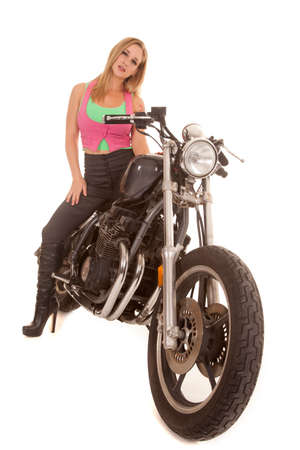 A woman is sitting on a motorcycle with a serious expression. photo