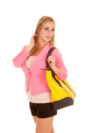 A woman in a pink jacket is holding a yellow bag looking over her shoulder. photo