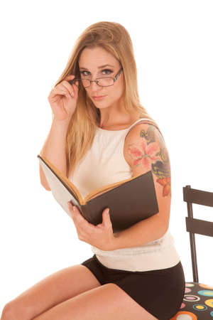 A woman is holding a book looking over her glasses. photo