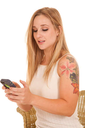 A woman with a tattoo is holding a phone texting.