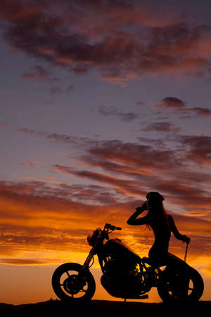 A silhouette of a woman sitting on the back of the bike. photo
