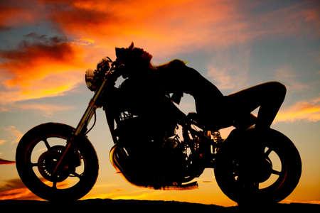 motorrad frau: Eine Silhouette einer Frau, die Verlegung zur�ck auf ihrem Motorrad.