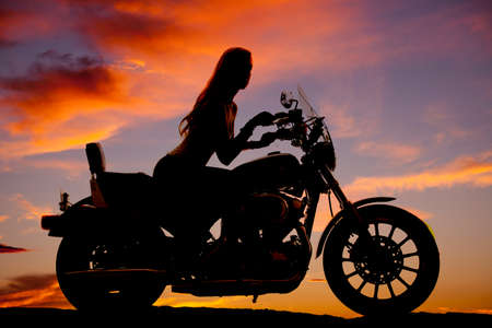 A silhouette of a  woman sitting on her motorcycle. Stock Photo