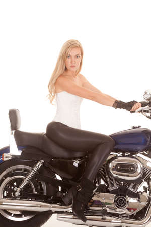 A woman sittingon a motorbike in her tight fitting black pants. photo