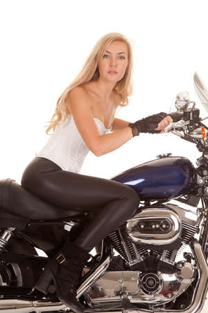 A woman sitting on her bike looking serious at the camera.