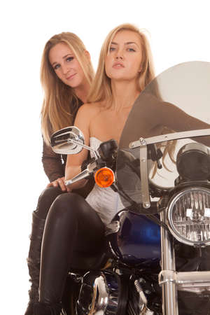 Two women are sitting on a motorcycle with a serious expression. photo