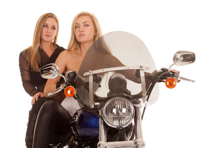Two women are sitting on a motorcycle. photo