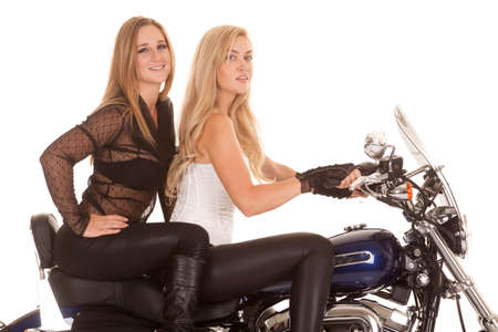 A close up of two women riding on a motorcycle. Foto de archivo