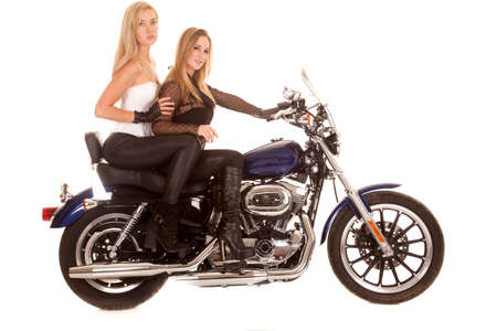 Two women are sitting on a motorcycle from a side view. photo