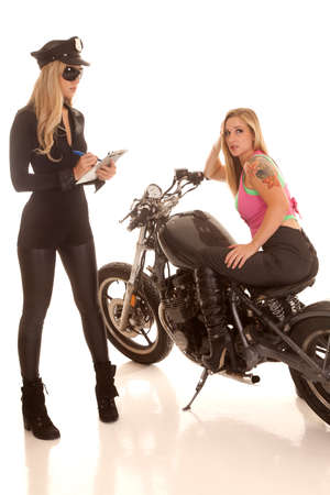 motor officer: A woman is getting a ticket from riding her motorcycle. Stock Photo