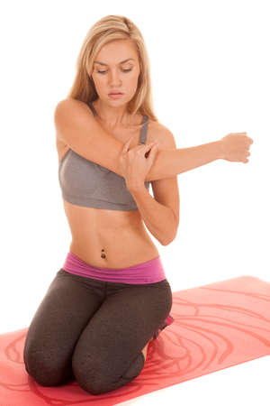 A woman is sitting on a red yoga mat stretching her arm. photo
