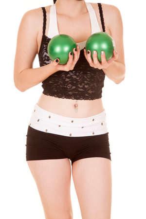 A woman is holding green fitness balls by her chest.