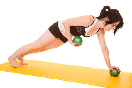 push: A woman is doing push ups while holding green balls.