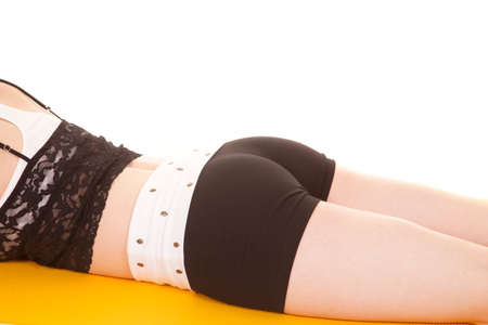 A woman is laying on a yellow yoga mat.