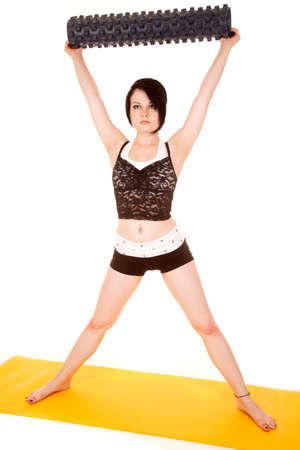 A woman is holding a fitness roll over her head.