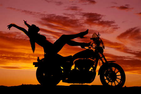 A silhouette of a woman leaning back on her bike with her arms up and feet up. photo