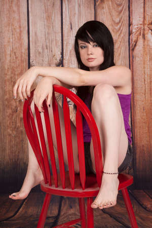 A woman sitting on her chair backwards with  a serious expression. photo
