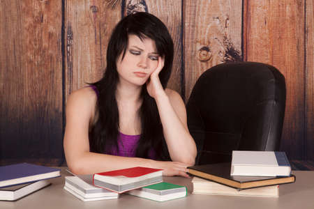 a woman not really wanting to study all the books on the table. Imagens