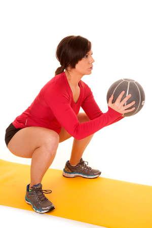 Eine Frau macht eine Kniebeuge mit ihrem Medizinball mit einem ernsten Ausdruck auf ihrem Gesicht.