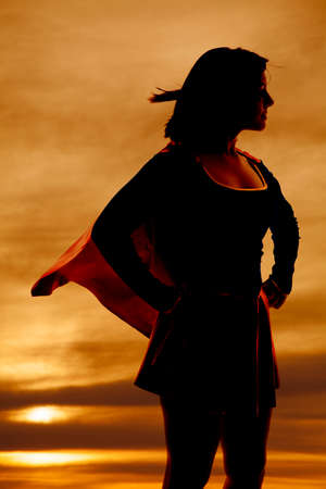 A silhouette of a woman in her super hero out fit cape flying. photo