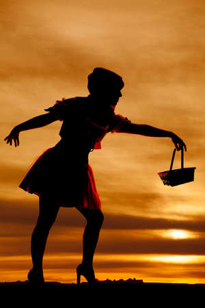 a silhouette of a woman in red with a basket. photo
