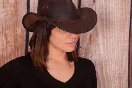 cowgirl hat: Un primer plano de una mujer en su sombrero de vaquera ocultando sus ojos. Foto de archivo