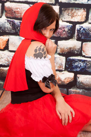 A woman in her red hood and dress with a wolf paw print on her shoulder. photo