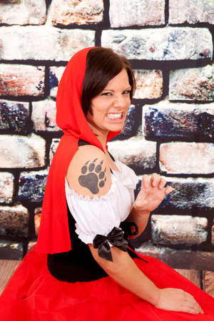 A woman in her red hood and wolf paw tattoo on her shoulder growling. photo